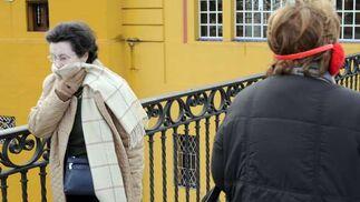 Una mujer se tapa la cara con una bufanda.