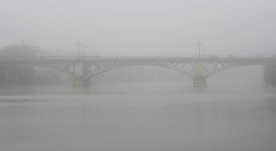 El Puente de Triana, apenas esbozado por la niebla.  Foto: Juan Carlos Muñoz