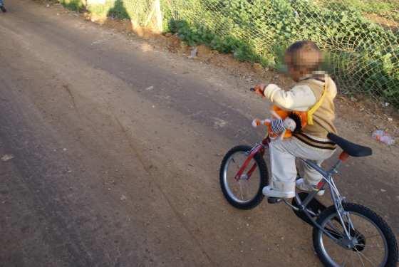 Un niño juega con su bicicleta nueva.