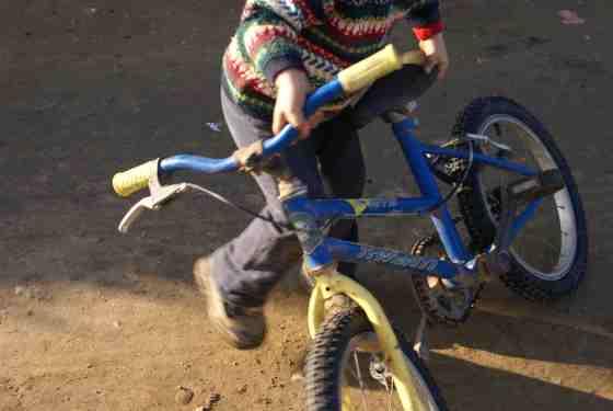 Un niño juega con una bicicleta.