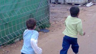 Dos niños corren por las calles de asentamiento.