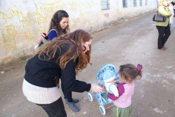 Una pequeña juega con su muñeco nuevo y el carrito.