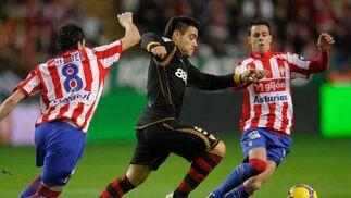 Duscher pugna con el balón frente a dos rivales.  Foto: Felix Ordo?
