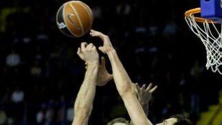 Xavi Rey salta para encestar pese a la negativa de Van Den Spiegel.  Foto: Antonio Pizarro