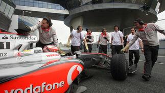 Los mecánicos de McLaren, también con guantes para evitar las descargas del 'Kers', introducen el monoplaza en el box del equipo.  Foto: J. C. Toro