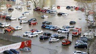 Efectivos de Policía Municipal y Bomberos tratan de retirar los vehículos que han quedado atrapados por el agua en un aparcamiento en el barrio pamplonés de la Rochapea.  Foto: EFE