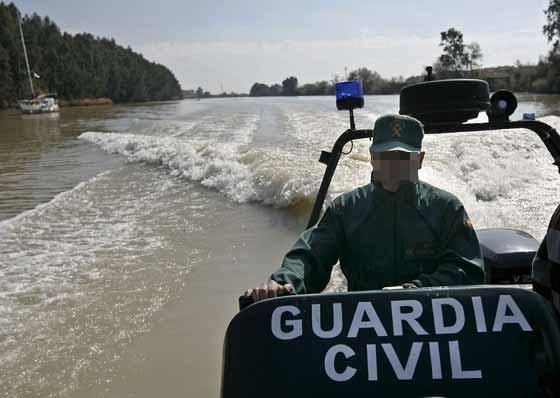 Una lancha de la Guardia Civil, a la altura de Gelves.  Foto: Eduardo Abad (Efe)