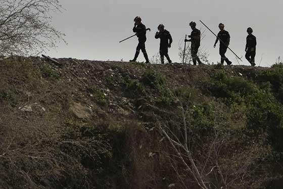 Miembros de la UME rastrean a pie los márgenes del río.  Foto: Eduardo Abad (Efe)