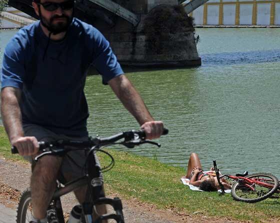 Un ciclista por el río con una joven tumbada en el césped de la orilla junto.  Foto: Victoria Hidalgo/Juan Carlos Vázquez