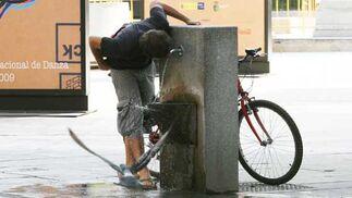 Un joven para su bicicleta para refrescarse en una de las fuentes públicas instaladas por la ciudad.  Foto: Victoria Hidalgo/Juan Carlos Vázquez