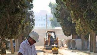 Un trabajador echa agua sobre uno de los huecos del pavimento./ Belén Vargas