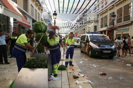 Operarios de limpieza recogen basura en Calle Larios.