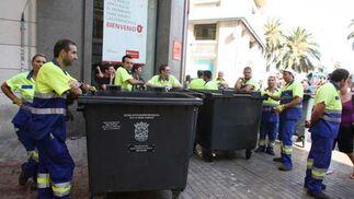 Trabajadores de la limpieza esperan para recojer la basura.