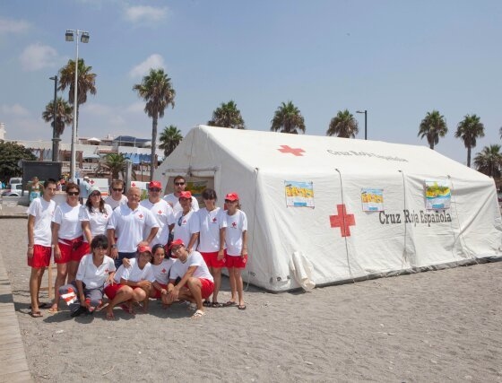El grupo de voluntarios participantes posa junto al hospital de campaña en la playa de Salobreña.  Foto: Salvador Rodriguez Caña