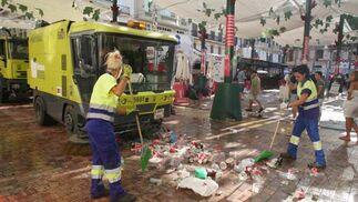 Dos trabajadoras de la limpieza recojen vasos en la Plaza de la Constitución, después de la feria de día.