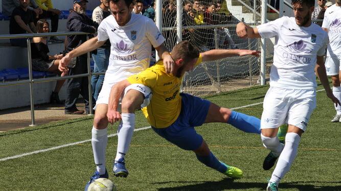 Orellana controla el balón junto a Alberto y un jugador del Conil que cae al césped.