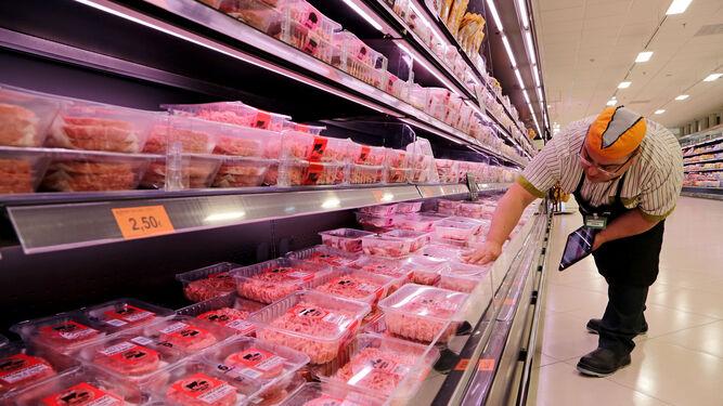 Un trabajador coloca el surtido de carne.