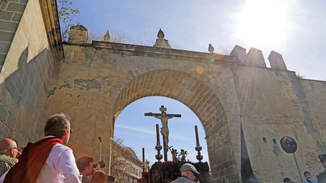 El Cristo del Perdón pasa bajo el Arco del Arroyo, esa especie de frontera que le introduce de pleno en el casco antiguo de Jerez.