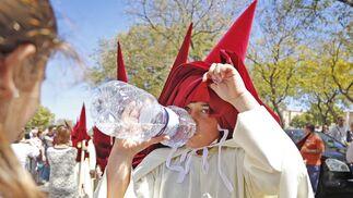 Las botellas de agua, tanto de la propia hermandad como de los familiares, no faltaron en el cortejo del Soberano Poder.