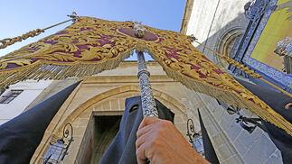Un nazareno de las Tres Caídas porta en la salida procesional de ayer un estandarte mariano.