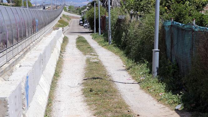 Un tramo de calle sin terminar, junto a las vías del tren.