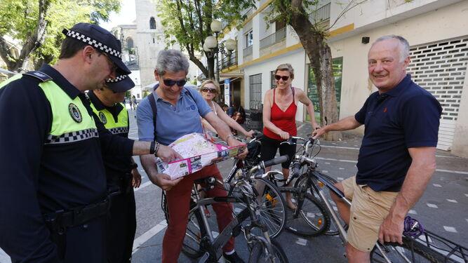 Una patrulla de la Policía Local orienta a unos turistas en Plateros.