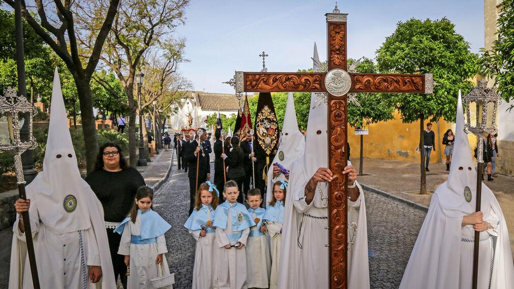La cruz de guía abriendo el cortejo ayer, con los nazarenos vestidos de blanco impoluto y algunos pequeños acompañando a los hermanos del Resucitado.