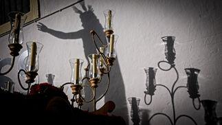 Los candelabros del Resucitado, con la proyección de la sombra de la talla detrás.