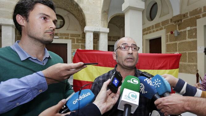Martín Aubarrea habla a los medios mientras que una mujer despliega detrás una bandera de España en la Casa de Iberoamérica.