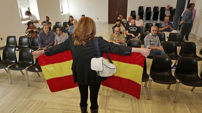Una mujer despliega  una bandera de España en la Casa de Iberoamérica.