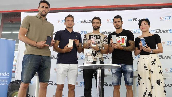 Los futbolistas muestran el móvil junto a la gerente de ZTE.