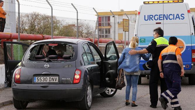 Un policía local acompaña a una mujer que, tras sufrir el impacto de una rama en su vehículo, resultó herida.