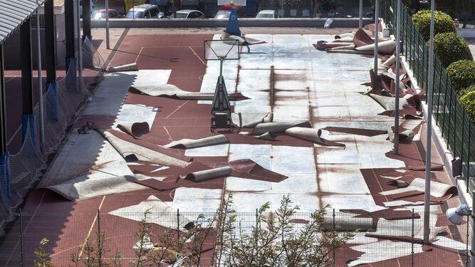 Operarios de mantenimiento retiran la arena acumulada en el paseo marítimo de Cádiz, a la altura de la calle Brasil.