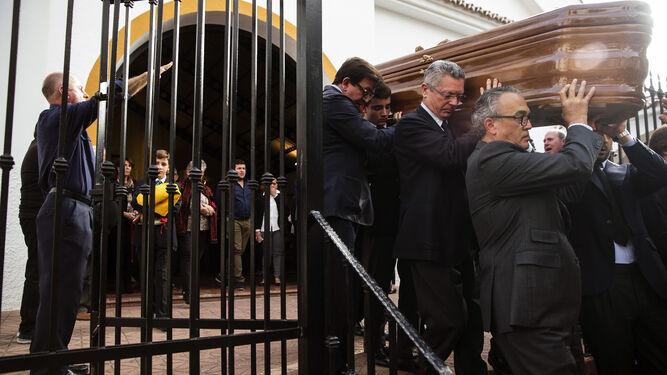 """Familiares, entre ellos Alberto Ruiz Gallardón, portan el féretro mientras un hombre entona el """"Cara al Sol"""" a la salida del funeral."""