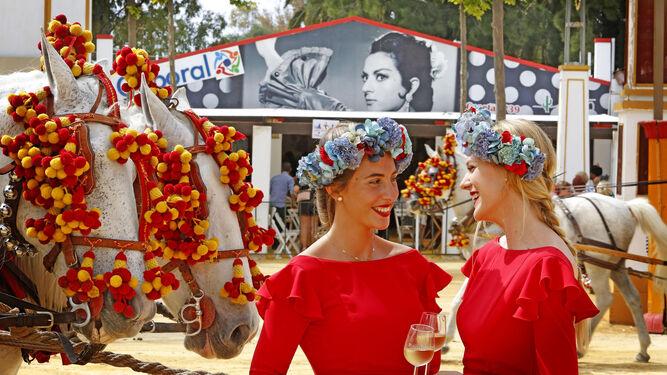 Dos chicas Fundador, ante  un coche de caballos  ayer en el Rea