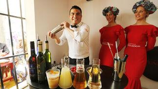 Ricardo González, bartender de FIZZ, elabora uno de los cócteles de Harveys junto a dos azafatas de Fundador en la caseta de la bodega en la Feria.