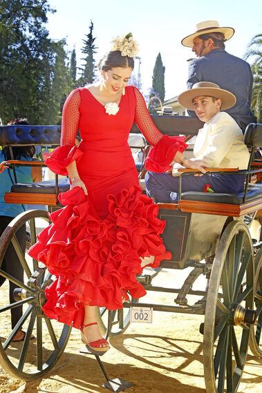Una joven vestida de faralaes baja de un coche de caballos.