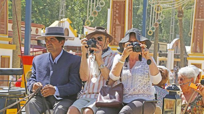 Una pareja de visitantes fotografía el Real desde las alturas de un coche de caballos.