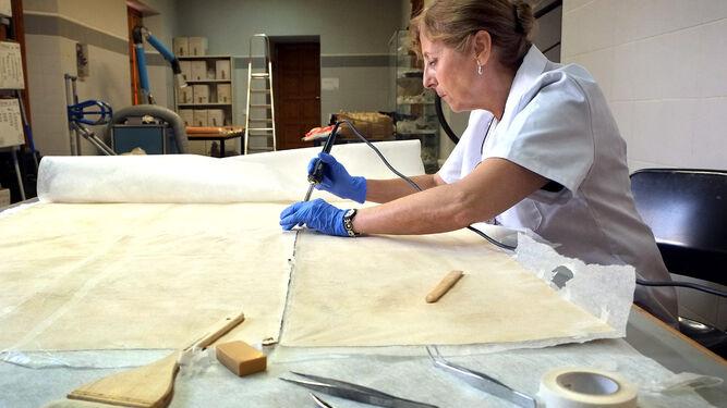Una empleada trabajando en la restauración de un cartel.