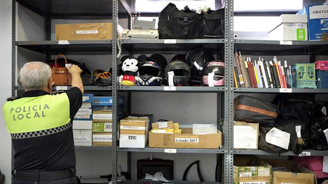 Un agente coloca un bolso en una de las estanterías.