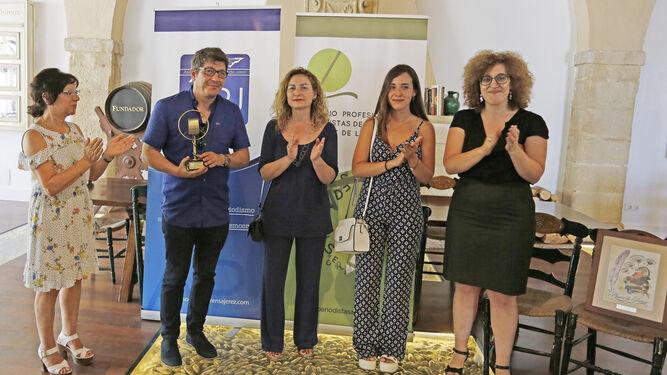 Adrián Domínguez Bezares sostiene el premio tras su concesión junto al comisario y la presidencia del acto.