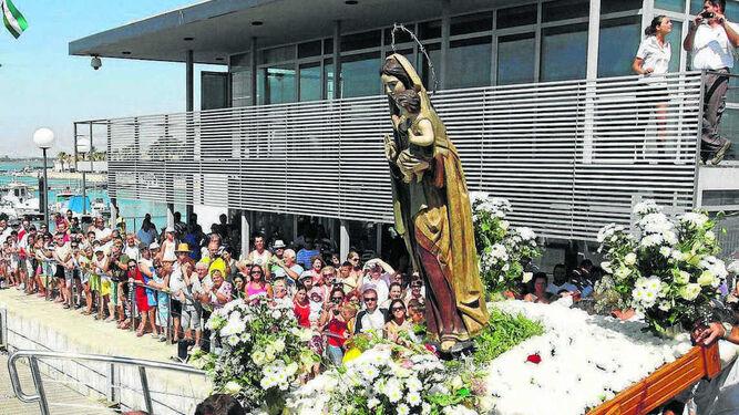Hermanos cofrades de Chiclana subiendo a la Virgen del Carmen atunera en el barco para su recorrido por mar