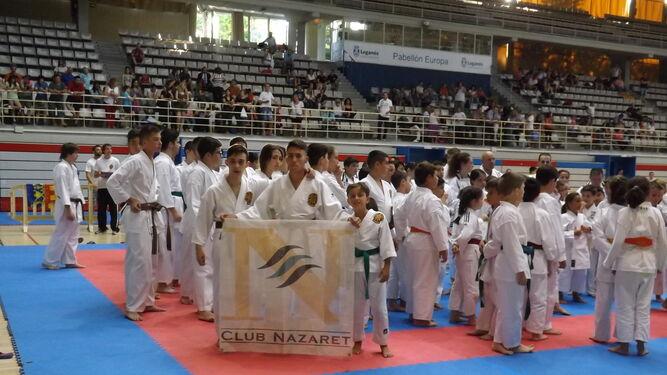 Algunos deportistas del Club Nazaret posan con la bandera del club.