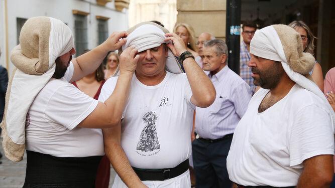 Un grupo de costaleros se ponen la ropa antes de hacer el primer relevo por la zona de la plaza de la Asunción.