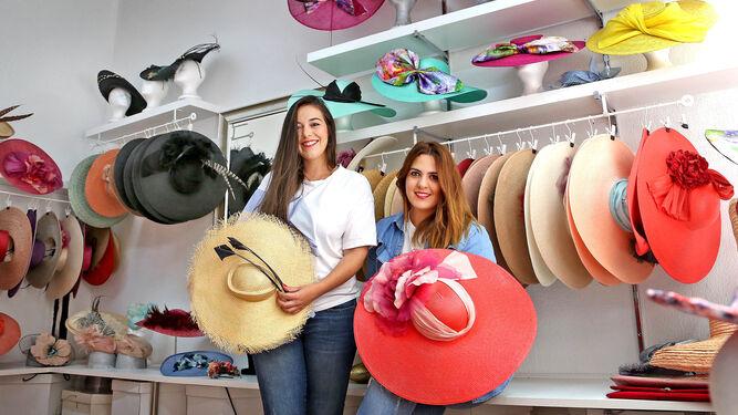 Laura y Ana posan durante la realización de la entrevista en su tienda de la calle Honda junto a sus tocados y pamelas.