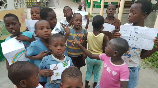 1. Los niños del 'Lar Siloé' enseñan los dibujos que han hecho para sus padrinos y madrinas. 2,3 y 4. Cada año, los más pequeños colorean y dibujan y tienen la oportunidad de comunicarse con las personas que les apadrinan mandándole cartas y dibujos a través de los cooperantes cuando estos viajan allí.