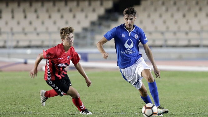 Bocanegra, portero del Cartaya, sale para despejar de puños un balón en presencia de Jorge Herrero, que al final le hizo un gol, y uno de sus defensas.