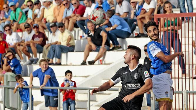 Guerrero salta junto a un futbolista del Alcalá para intentar despejar el balón de cabeza.