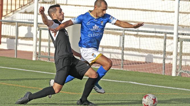 José Vega, que dejó su puesto a Javi, intenta superar a un jugador del Alcalá.