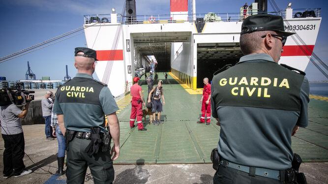 Miembros de la Guardia Civil vigilan el embarque en el Albayzin mientras una pasajera muy enfadada se queja de la rocambolesca situación ante los periodistas.